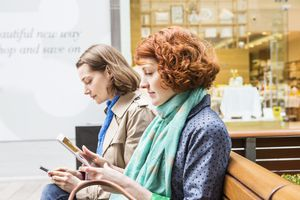 Women sitting in shopping area looking at internet