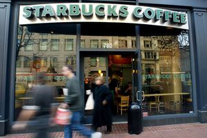 People walk out of a Starbucks coffee shop.
