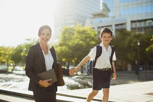 A business woman walking with her young son in an urban setting