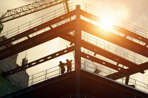 Construction workers silhouetted against the sun