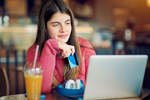Teenage girl is shopping online in a cafeteria