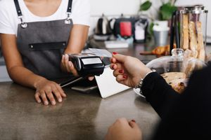 Cropped Image Of Woman Hand Holding Credit Card While Making Payment In Cafe