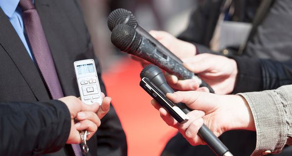 Midsection Of Reporters Holding Microphone By Businessman