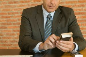 A CFO, or chief financial officer, sits at a desk with a brick wall behind him