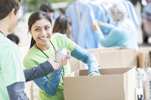 A woman passing out canned goods