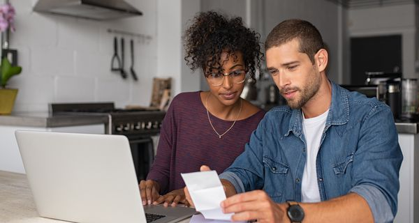 Couple looks over their finances as they consider a refi.