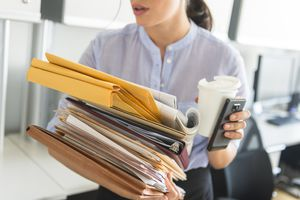 A business woman holding stack of documents in office.