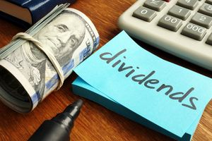 A roll or money laying next to a sticky note with the word dividends.