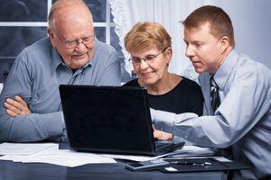 A man explaining something on a laptop to senior couple.