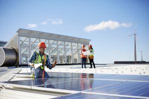 Engineer installing solar panels at sunny power plant