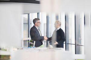 Men Shaking Hands Next to Desk in Office