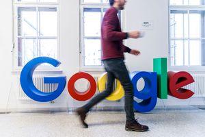 man walks in front of Google logo