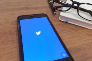 The Twitter logo displayed on a smartphone sitting on a desk.