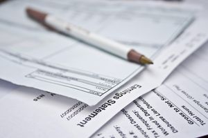 Pencil on pile of pay statements