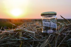 Jar Of Coins With Pension Text On Straw During Sunset