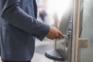 Close-up of businessman withdrawing money at an ATM