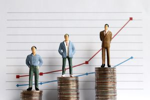 Miniature people standing on a pile of coins in front of a graph.