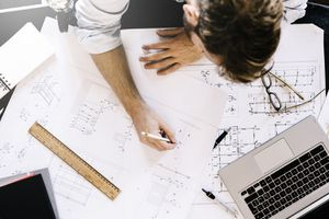 Man Working on Construction Plan at Desk