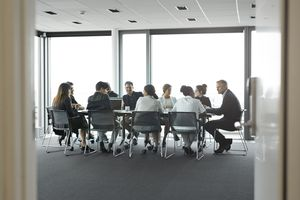 Co-workers having meeting with laptop in conference room