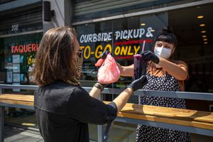 Masked restaurant worker and customer picking up food curbside during the Covid-19 pandemic.