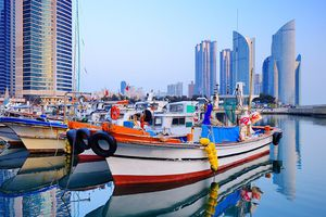Fishing boats moored in front of the sleek, modern skyline of Busan, South Korea.
