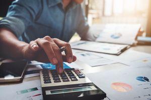 Business man using calculator analyzing costs.