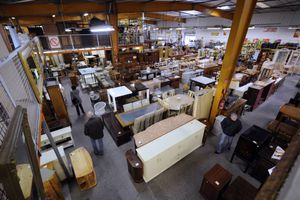 People walk past house furnishings in consignment store