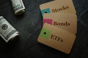 ETF (Exchange Traded Funds), Stocks and Bonds paper tags with cash on dark background.