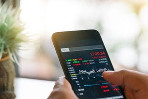 Businessman trading stocks with smarthphone and check stock market data