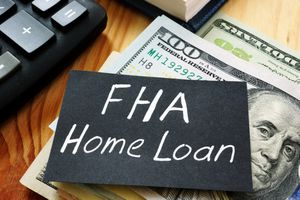 Text sign showing hand written words FHA Home loan with one hundred dollar bills