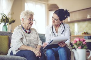 White-haired woman and nurse sit on a couch, going over paperwork