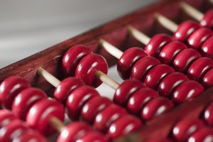 Closeup of red beads on a wooden abacus