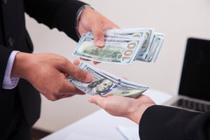 Businessman Giving Money to His Partner While Making Contract
