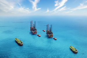 Aerial view of two oil rigs in the ocean surrounded by ships