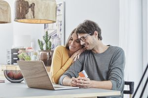 Smiling Couple With a Card Using Laptop on Table at Home