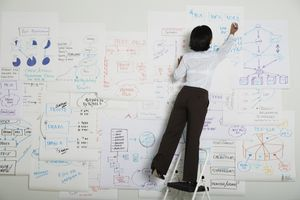 Woman standing on a step ladder writing on a flow chart made of papers on a wall