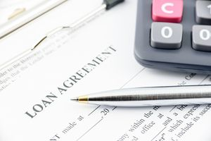 A loan agreement with a pen and calculator