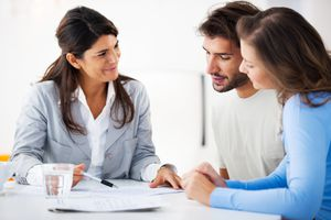 A financial consultant presents bank investments to a young couple.