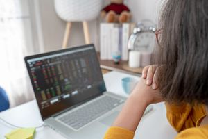Woman sits at desk while looking online trading screen on laptop