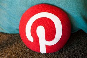 Red Pinterest logo on a pillow.