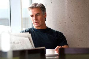 Silver-haired man reading newspaper
