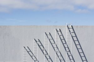Row of different sized ladders leaning against a concrete wall