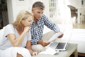 Man and woman looking confused over paperwork