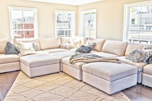 A home with staging of large beige, neutral white couches and throw rugs with pillows.