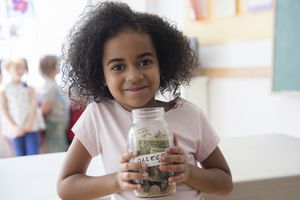 Little girl with big glass jar labeled