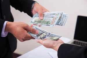 Businessman giving money to his partner while making contract,