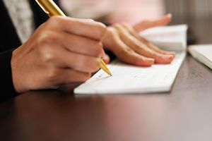 Cropped Hand Of Woman Signing On Check Over Table