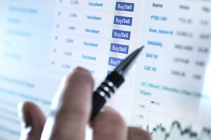 hand of a stockbroker holding a pen in front of a screen showing the option to buy or sell stocks