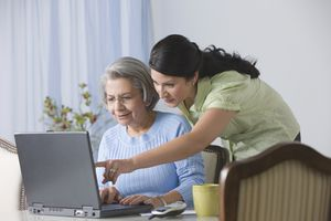 A young woman shows an older woman how to use a laptop.