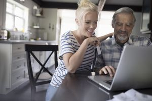 An elderly man and woman looking at a laptop